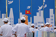 A group of men in white unifroms stand by a billboard depicting the Hanoi skyline, Hanoi, Vietnam, Southeast Asia