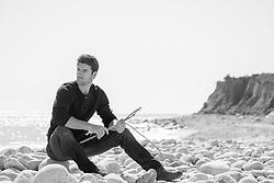 hot man sitting on a rocky beach