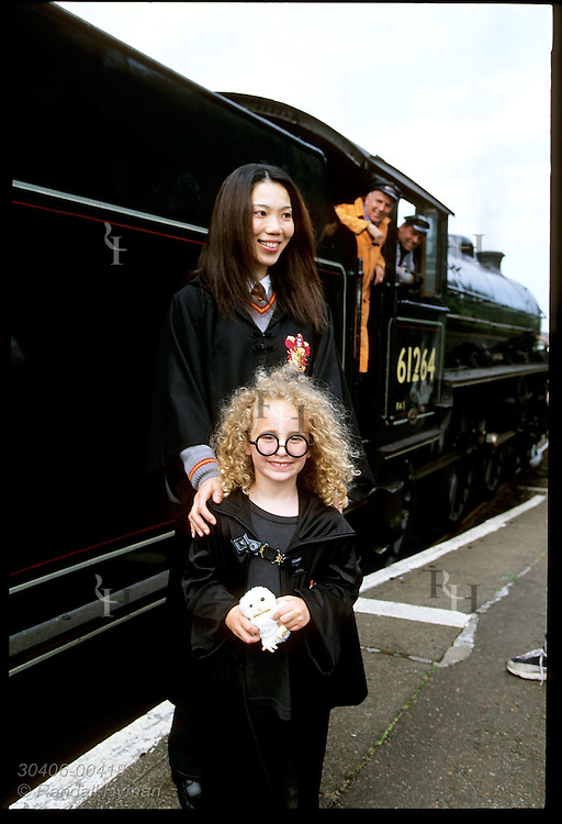 Two Harry Potter fans, American girl and Japanese woman, pose at station after movie-fame steam train ride; Ft William, Scotland.