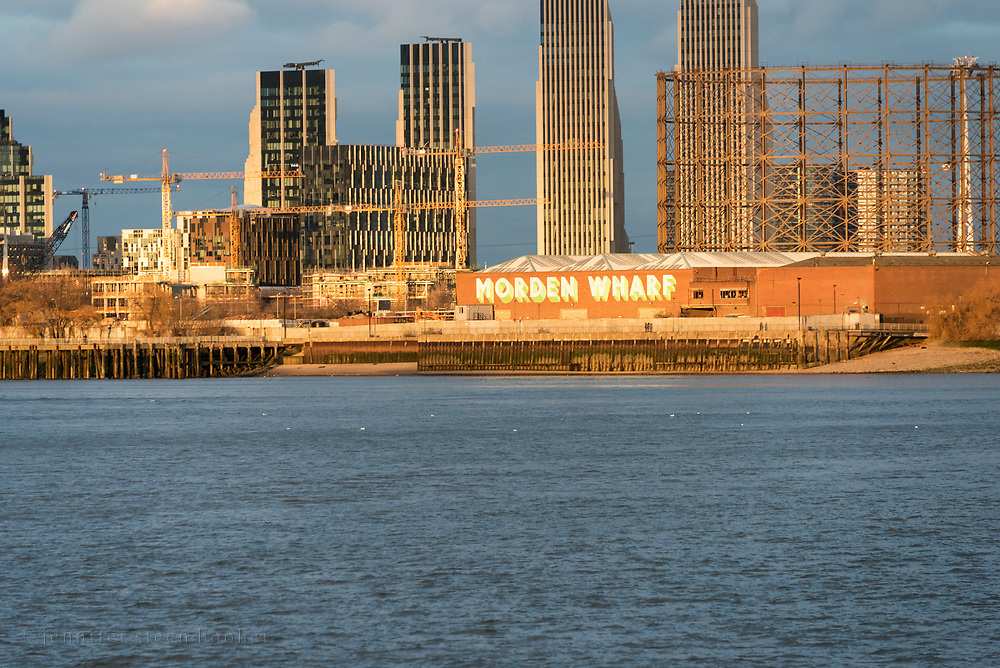 Morden Wharf in late afternoon sun, looking east from Greenwich, London, UK