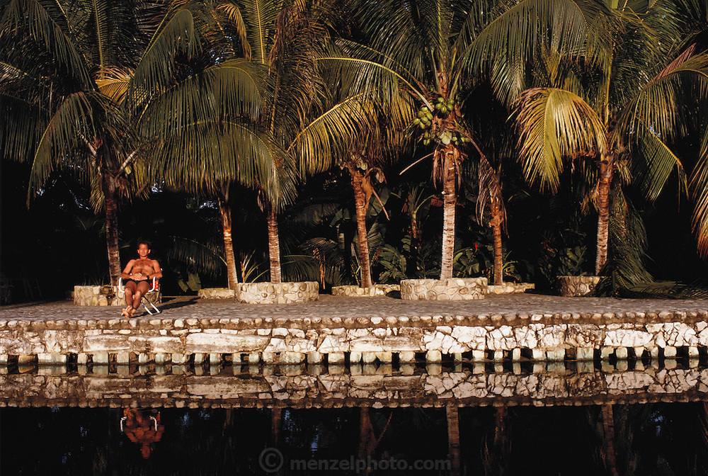Sitting poolside with palm trees at the Chan Kah Cabanas Hotel. Palenque, Mexico. Near Mayan ruins of Palenque.