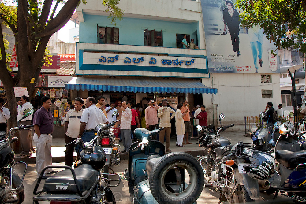 Patrons with cups of tea in their hands stand outside a popular tea and breakfast restaurant on a weekend in Bangalore, India.