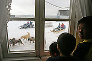 (MODEL RELEASED IMAGE). Abraham, Martin and Belissa break away from watching MTV to watch dogsled teams and travelers on a skidoo hauling supplies in a sled pass by the window of their house. (Supporting image from the project Hungry Planet: What the World Eats.) The Madsen family of Cap Hope village, Greenland is one of the thirty families featured, with a weeks' worth of food, in the book Hungry Planet: What the World Eats.