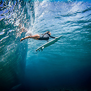 Female surfer duck diving under a wave in clear blue ocean water in the Kingdom of Tonga.