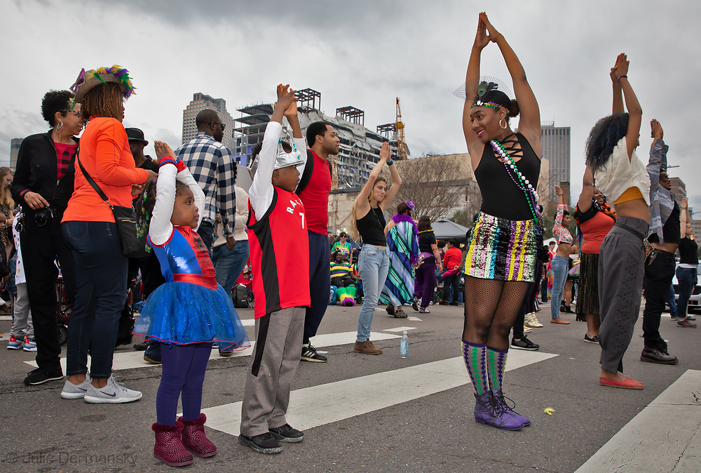 People doing yoga celebrating Mardi Gras in New Orleans on Mardi Gras day near the partially collapsed Hard Rock Cafe  Hotel.The hotel collapsed while it was still under construction  on Oct. 12, 2019, killing at least three workers. Two of the bodies remain trapped inside.