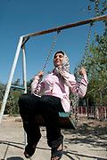 Afghanistan. Mazar-e-Sharif high school. Girl aged 17 playing on a swing