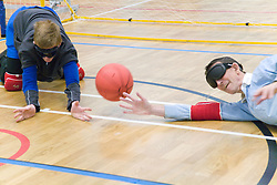 Team players trying to stop ball during a Goalball game; a threeaside game developed for the visually impaired and played on a volleyball court,  A specially adapted ball containing an internal bell is used,