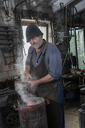 Blacksmith cooling down hot iron bar at workshop, Bavaria, Germany