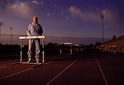 An elderly track coach stands at a hurdle at sunrise waiting for his team to show up for practice