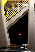 Full moon seen below the stairs of the Jamestown Ferry at night