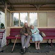 An elderly couple sleep on a seaside shelter's bench on the promenade at the southern English resort of Southend-on-Sea, Essex. As the gentleman clasps both hands and with his stick propped up on the seating, the lady has hooked her handbag around an elbow, her arms folded over themselves as she snoozes for an afternoon catnap. They are the epitome of marital loyalty, a lifetime commitment of stability, love and affection.