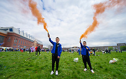 Glasgow, Scotland, UK. 15 May 2021. Thousands of supporters and fans of Rangers football club descend on Ibrox Park in Glasgow to celebrate winning the Scottish Premiership championship for the 55nd time and the first time for 10 years. Smoke bombs and fireworks are being let off by fans tightly controlled by police away from the stadium entrances.Pic; Young fans with orange smoke flares. Iain Masterton/Alamy Live News