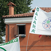VENICE, ITALY - SEPTEMBER 18:  Members of Lega Nord cover the famous window with Italian flag of Lucia Massarotto which has become the symbol of protest against Lega Nord separatist and racist ideology on September 18, 2011 in Venice, Italy. The Northern League rally is held to call for the independence of Northern Italy, during which the leader of Lega Nord pours water from the River Po in the north of Italy into the Venetian Lagoon as a symbolic rite known as Rito dell'ampolla.