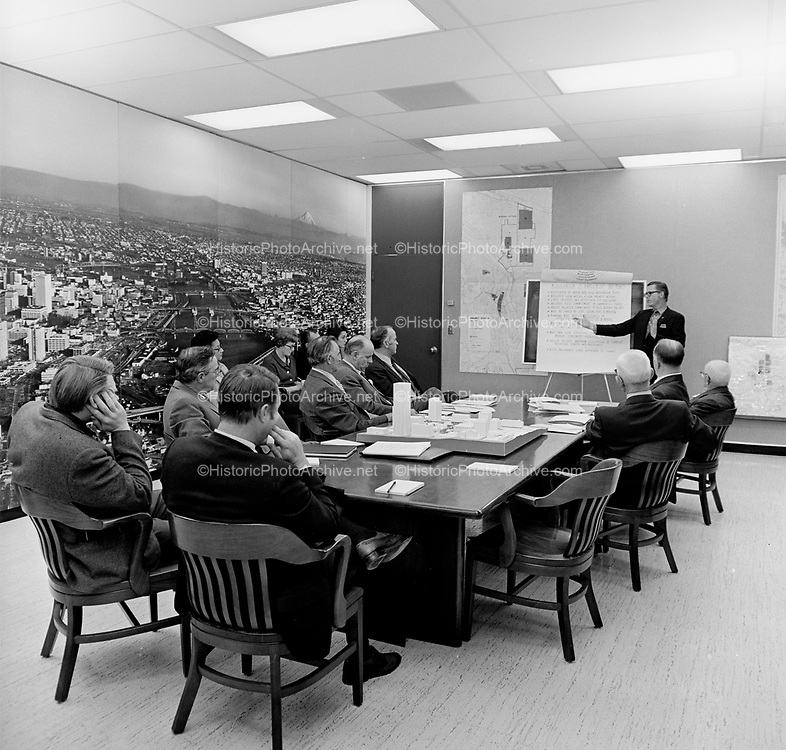 """Y-711108A-11.  Portland Development Commission board meeting. November 8, 1971. Includes scale model of downtown on table. Map of Albina and Model Cities criteria. Frame 11 chart: """"Memorandum of Agreement Key Points … Negotiated by mayor and H. U. D. area/regional reps. Reflects local needs & local priority action. Lists projects and activities for one year. Includes H. U. D. commitment of earmarked funds. Needs related commitment of H. U. D. housing dollars. Must be linked to Local future year planning. Planning must involve residents of affected area and city as a whole. Must reflect National  (illegible) Environmental preservation (illegible. Most show local structure for (illegible) manage, coordinate evaluate (illegible). Should reflect maximum utilization of current individual staffs and procedures. H. U. D. encourages local approach to format."""""""