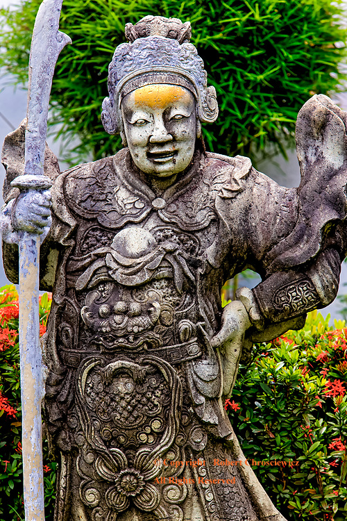On Guard: A Chinese style stone statue stands guard, holding a pike, in the gardens of the Imperial Grand Palace, Bangkok Thailand.