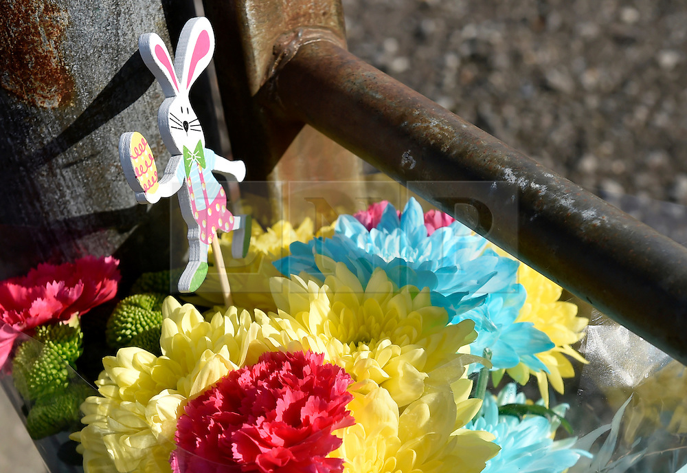 """© Licensed to London News Pictures. 27/03/2016. London, UK. Flowers are left at the entrance to Harlow Town Park after a girl died when a bouncy castle she was playing in """"blew away by some distance"""". Two people are being held on suspicion of manslaughter by gross negligence following the incident which took place in Harlow Town Park in Essex. Photo credit : Hannah McKay/LNP"""