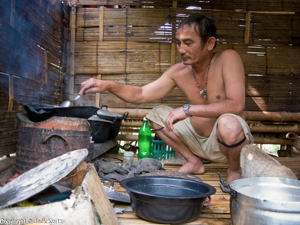 18 FEBRUARY 2008 -- BONG TI, KANCHANABURI, THAILAND:  A Karen Christian man makes dinner for his family in a Karen refugee village near the Bamboo School in Bong Ti, Thailand, about 40 miles from the provincial capital of Kanchanaburi. Sixty three children, most members of the Karen hilltribe, a persecuted ethnic minority in Burma, live at the school under the care of Catherine Riley-Bryan, whom the locals call MomoCat (Momo is the Karen hilltribe word for mother). She provides housing, food and medical care for the kids and helps them get enrolled in nearby Thai public schools. Her compound is about a half mile from the Thai-Burma border. She also helps nearby Karen refugee villages by digging water wells for them and providing medical care. Thai authorities have allowed the refugees to set up the village very close to the border but the villagers are not allowed to own land in Thailand and they can't legally leave the area to get jobs in Thailand.    Photo by Jack Kurtz