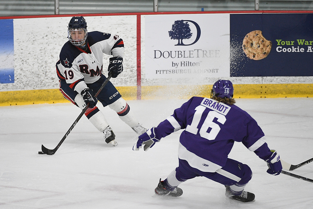 PITTSBURGH, PA - MARCH 12: Randy Hernandez #19 of the Robert Morris Colonials controls the puck as Jared Brandt #16 of the Niagara Purple Eagles defends in the second period during Game One of the Atlantic Hockey Quarterfinal series at Clearview Arena on March 12, 2021 in Pittsburgh, Pennsylvania. (Photo by Justin Berl/Robert Morris Athletics)