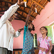CAPTION: After-School Club (ASC) Coordinator Kalappa demonstrates a paper helicopter to his group, after Chowdamma - who has a learning disability - asked him how helicopters work. Kalappa says that one of the ways he makes the club more inclusive for Chowdamma is that he finds ways to explain principles as visually as possible. LOCATION: Marialla (village), Kasaba (hobli), Chamrajnagar (district), Karnataka (state), India. INDIVIDUAL(S) PHOTOGRAPHED: From left to right: Kalappa, Chowdamma and Kavya M.