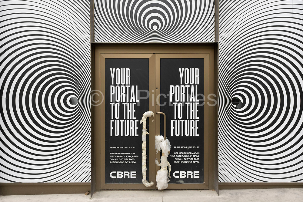 Empty shop with an optical spiral pattern advertising that inside could be a your portal to the future on Bond Street on 25th May 2021 in London, United Kingdom. These high end brands are seen next to each other on a very ordinary wall. Bond Street is one of the principal streets in the West End shopping district and is very upmarket. It has been a fashionable shopping street since the 18th century. The rich and wealthy shop here mostly for high end fashion and jewellery.