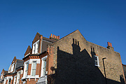 The shadow of a neighbours chimneys on the side of an end-of-terrace house in south London, on 30th January 2019, in Herne Hill, Lambeth, London, England.