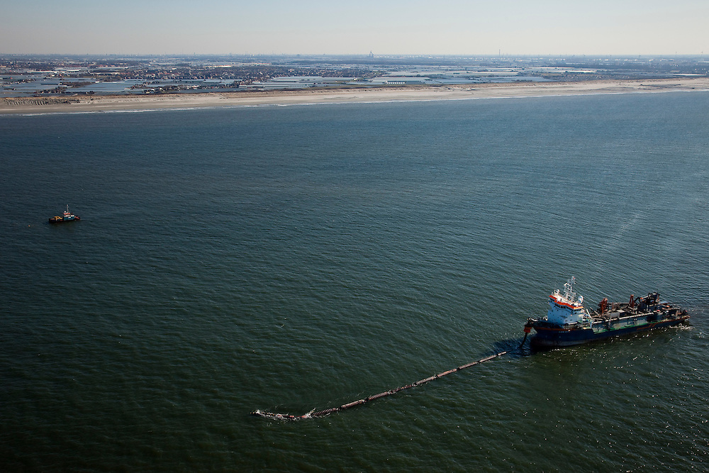 Nederland, Zuid-Holland, Monster, 18-03-2009; Sleephopperzuiger HAM 311 van de Hollandsche Aanneming Maatschappij voor de Kust van Delfland. Het schip is verbonden met een persleiding en spuit zand op het strand. Deze zandsuplletie dient om de kust te versterken. Door de geringe diepgang kan het schip tot vlak onder de kust werken. Westland met kassen aan de horizon.Hopper dredger HAM 311 at work at the coast of Delfland. The ship is connected to a high pressure pipes and sprays sand on the beach. The sand-supplementation serves to strengthen the coast. Due to the small gauge, the ship can work near the coast..Swart collectie, luchtfoto (toeslag); Swart Collection, aerial photo (additional fee required); .foto Siebe Swart / photo Siebe Swart