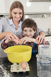Schoolboy cracking an egg into a mixing bowl in home economics class, Bavaria, Germany