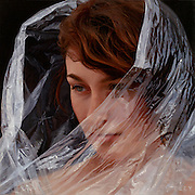 She IS an oil painting: Artist's amazingly detailed works of 'hyper-realistic' paintings that look like photographs<br /> <br /> At first glance, you think you are seeing a photo.<br /> But peer closer and maybe - just maybe - you can see the paint-strokes that belie the fact that these are actually hyper-realistic paintings.<br /> Each exquisitely detailed piece of work shows naked subjects wrapped in plastic foil - meaning Australian artist Robin Eley must pay close detail to each fold, each reflection, and the changing tones between plastic and flesh.<br /> It takes many many hours for Eley to produce a portrait, with his largest works taking five weeks apiece - working 90 hours per week.<br /> <br /> Born in London in 1978, but raised in Australia from the age of three, the artist has been exhibited in London and New York, among others, and he has been both a runner-up and highly-recommended in the Australian Doug Moran National Portrait Prize.<br /> Moving from commercial illustrations to portrait work a few years ago, one of his key themes is isolation, and he recently said: 'I was really thinking, getting down to the heart of what it was I wanted to say before recreating and re-imagining things that made me feel something.'<br /> <br /> Robin added: 'One of those things was the way we are experiencing isolation in the modern world.<br /> 'I'm the son of a parents who met in an overseas country neither was from.<br /> 'Mum was from China and had moved to London, isolated from her friends and family. Dad was from Adelaide. Today the isolation is different from theirs.<br /> 'We are so connected we don't even need to connect. Modern isolation is the technology we have actively embraced. <br /> 'We are all on Facebook where we don't have to ask our friends how they're going because we can see what they're doing.'<br /> Cellophane is his medium for this - it is something you can see through but not feel through.<br /> He said: 'It is a seductive existence where qu