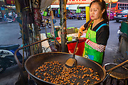18 SEPTEMBER 2013 - BANGKOK, THAILAND:  A vendor roasts chestnuts at a street stall in the Chinatown section of Bangkok. Thailand in general, and Bangkok in particular, has a vibrant tradition of street food and eating on the run. In recent years, Bangkok's street food has become something of an international landmark and is being written about in glossy travel magazines and in the pages of the New York Times.     PHOTO BY JACK KURTZ