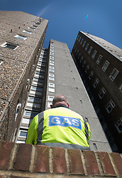 © Licensed to London News Pictures. 11/08/2017. London, UK. A gas worker stands on the Ledbury Estate as the gas supply is switched off. Residents on the Ledbury Estate in south London have been told they will have to leave their properties over the next few weeks. A structural survey carried out after the Grenfell fire found cracks that could lead to a collapse if a gas explosion occured in one of the flats. Photo credit: Peter Macdiarmid/LNP