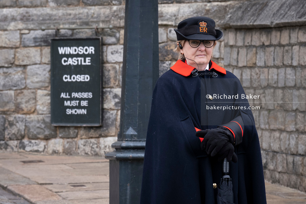 The day after the death at age 99 of Prince Phillip, the Duke of Edinburgh, consort to Queen Elizabeth II, a woman member of the Royal Household stands outside Windsor Castle where the Queen has been isolating throughout the Coronavirus pandemic, on 10th April 2021, in London, England.
