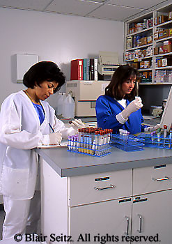Medical, African American and Caucasian Female Technicians, Blood Tests and Snack, Family Practice Lab