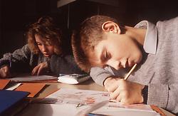 Two junior school pupils working at desk in classroom,