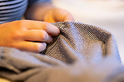 A young dressmaker woman uses a needle and thread to sew together a home-made dress that she's created from a pattern in her home, on 6th March 2021, in London, England.