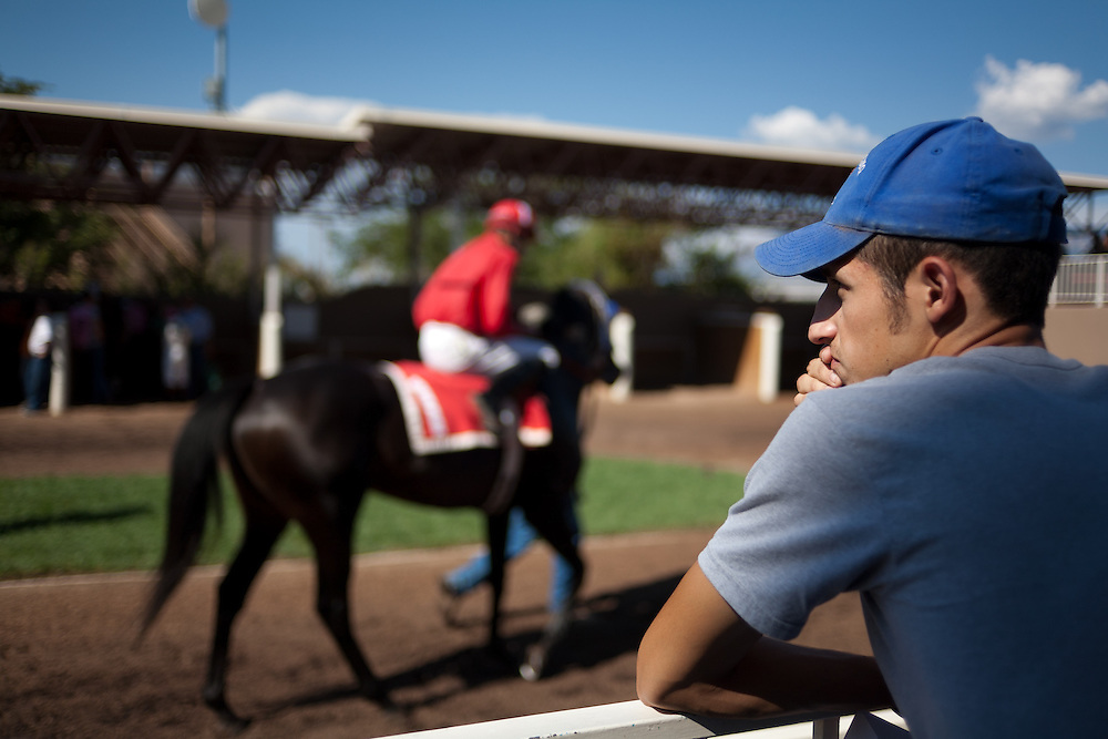 © Steven St. John / The Communicator..Jude Baca watches the horses and jockeys getting ready in the paddock after his race at The Downs at Albuquerque on Friday, Sept. 2, 2011.....