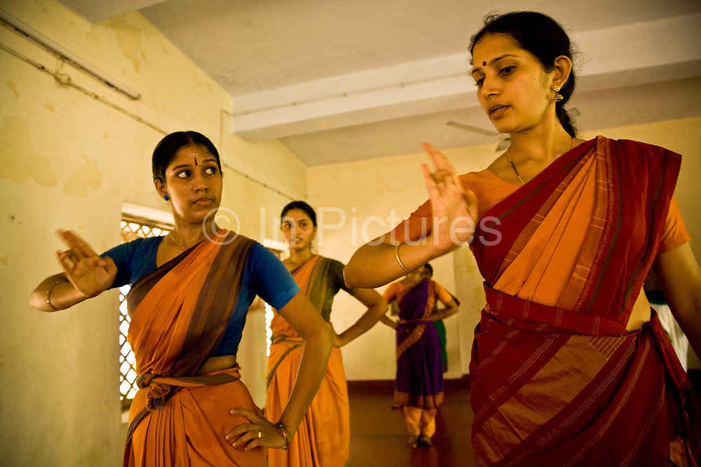 """Ganga Thampi, teaches young  trainee dancers  movement, rhythm and expression, known as """"nritya"""" as well as focusing on the gesture of the hands known as """"katakamukh"""" at the traditional and highly prestigious Kalakshetra school for the arts, Chennai. The school was founded in 1936 and due to its exacting and demanding schedule is considered India's formost classical dance academy of this ancient cultural art heritage that is informally known as """"temple dancing"""" and that dates back to the Natya Shastra, the 2000 year old text that lays down the principles of Indian dramatic theory and performance. Tamil Nadu, India."""