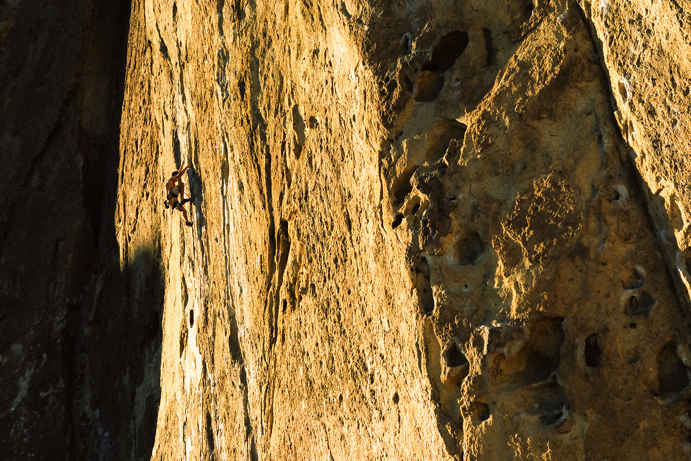 """A man climbing at Smith Rock State Park, Oregon. The route is called """"Magic Light"""", rated 5.11a at The Morning Glory Wall."""