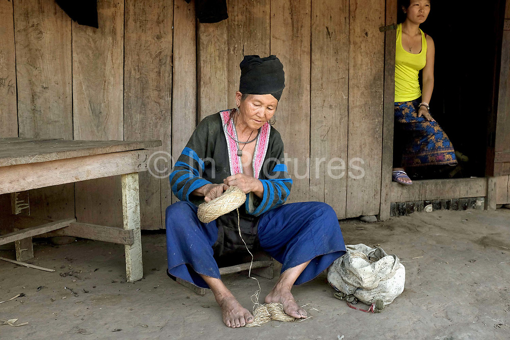 Wearing her traditional clothing, an elderly Hmong woman winds balls of hemp into one roll outside her home in Ban Chalern, Phongsaly province, Lao PDR. Making hemp fabric is a long and laborious process; the end result is a strong durable cloth with qualities similar to linen which the Hmong women use for their traditional clothing. In Lao PDR, hemp is now only cultivated in remote mountainous areas of the north. The remote and roadless village of Ban Chalern is situated along the Nam Ou river and will be relocated due to the construction of the Nam Ou Cascade Hydropower Project Dam 7.