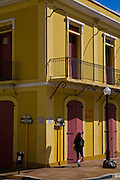 A woman walks past a colorful building in Mayaguez Puerto Rico