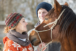 Young couple standing with horse in barn, Bavaria, Germany