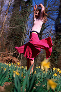 A912JA Girl dancing in daffodil woods in springtime