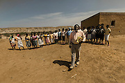 Tchikuteny with his wives, at the village. In Angola?s Namibe desert, at Giraul, in the Namibe province, Tchikuteny, from the Mucubal tribe, is the leader of a big family, maybe the biggest family in the world.<br /> He is the chief leader, the manager and responsible for the entire village. <br /> In his village, Tchikuteny lives nowadays with most of his big family, his 33 wives, that were once 43, but 10 left the village, and most of their descendants.<br /> Tchikuteny maintains the registry of all the new-borns, totalizing 154 sons, and his grandsons, that are around 60. Nowadays, 4 new babies are on the way, and 3 great grand children were born recently.<br /> Huge harmony, love and respect transpire in the village atmosphere. The sense of a community is the pillar of their sustainability and sustenance and their autonomy depends prominently on cattle and agriculture that is made by the villagers. Nevertheless, Tchikuteny village is in close connection with their surrounding communities. Children attend Giraul School and there is proximity and relations with the extended family that lives in the surroundings.<br /> Being the spiritual leader of the community, Tchikuteny is also responsible for the weekly religious works that happens in the village church. <br /> This big family opened his doors to share with us their daily lives.