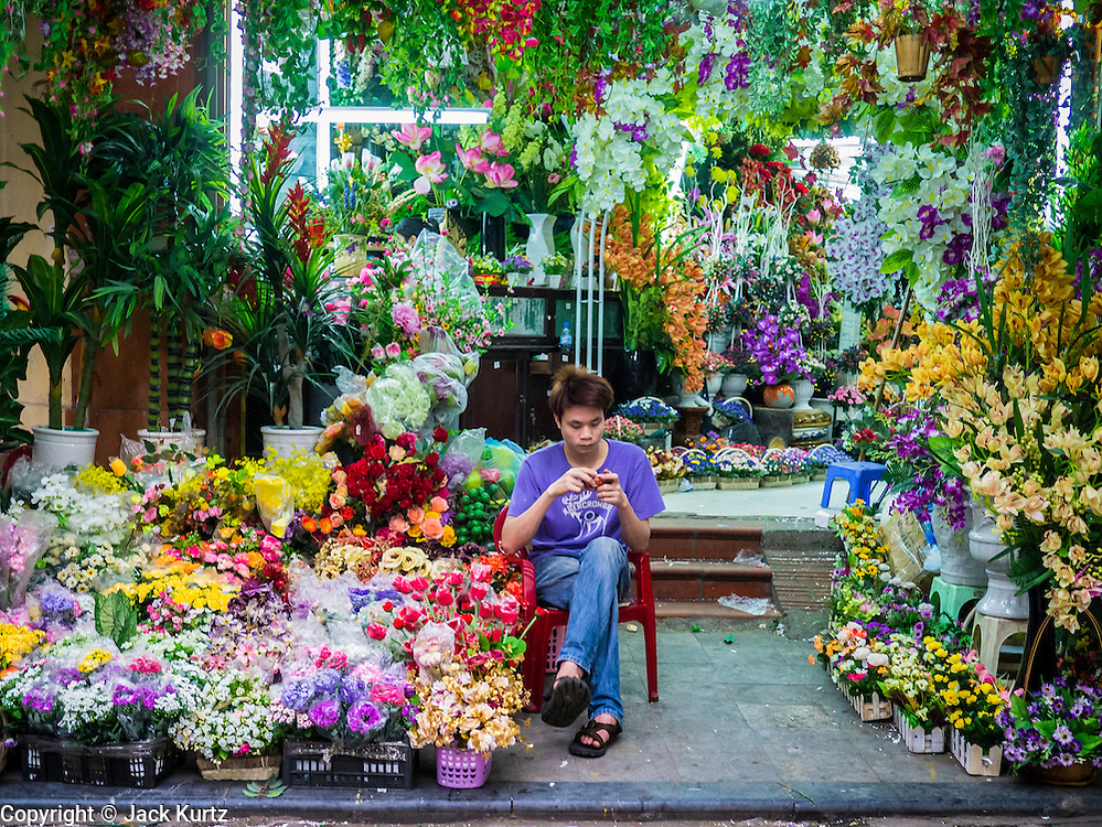 06 APRIL 2012 - HANOI, VIETNAM:   A man sells flowers in a market near the Long Bien Train Station in Hanoi, Vietnam. Hanoi is the capital of Vietnam and one of the oldest cities in Southeast Asia. It was established over 1000 years ago.    PHOTO BY JACK KURTZ