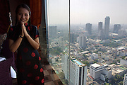 View over Bangkok from Shanghai 38 restaurant on the 38th floor of Sofitel Silom Bangkok. Waitress welcoming guests.