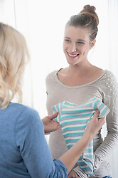 Two women girlfriend baby clothes holding happy