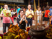 """07 AUGUST 2014 - BANGKOK, THAILAND:       People pray at an alter at Pek Leng Keng Mangkorn Khiew Shrine. Thousands of people lined up for food distribution at the Pek Leng Keng Mangkorn Khiew Shrine in the Khlong Toei section of Bangkok Thursday. Khlong Toei is one of the poorest sections of Bangkok. The seventh month of the Chinese Lunar calendar is called """"Ghost Month"""" during which ghosts and spirits, including those of the deceased ancestors, come out from the lower realm. It is common for Chinese people to make merit during the month by burning """"hell money"""" and presenting food to the ghosts. At Chinese temples in Thailand, it is also customary to give food to the poorer people in the community.    PHOTO BY JACK KURTZ"""