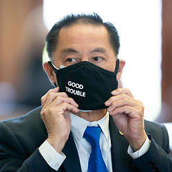 """The Texas House debating SB 7 late into the night  a controversial omnibus elections bill that would make changes to the way Texas elections are held. Rep. Hubert Vo, D-Houston, wears a mask channeling a Congressman John Lewis """"Good Trouble"""" quote."""