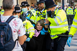 """© Licensed to London News Pictures. 25/08/2021. LONDON, UK. Police officers arrest a climate activist from Extinction Rebellion at Oxford Circus where a protest has taken place with people have glueing themselves to a pink wooden structure.  The event is part of the 'Impossible Rebellion' protest to """"target the root cause of the climate and ecological crisis"""" and are ongoing for two weeks until the Government agrees to stop all new fossil fuel investments.  Photo credit: Stephen Chung/LNP"""