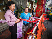 "18 JANUARY 2017 - BANGKOK, THAILAND: A woman shops for hand drawn Chinese New Year calligraphy in Bangkok's Chinatown district, before the celebration of the Lunar New Year. Chinese New Year, also called Lunar New Year or Tet (in Vietnamese communities) starts Saturday, 28 January. The coming year will be the ""Year of the Rooster."" Thailand has the largest overseas Chinese population in the world; about 14 percent of Thais are of Chinese ancestry and some Chinese holidays, especially Chinese New Year, are widely celebrated in Thailand.      PHOTO BY JACK KURTZ"