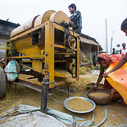 CAPTION: Potential customers of DESI Power operate a rice de-husking machine by the side of the road. LOCATION: Araria District, Bihar, India. INDIVIDUAL(S) PHOTOGRAPHED: Unknown.